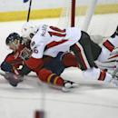 Florida Panthers' Brad Boyes (24) and Clarke MacArthur (24) battle for the puck while goalie Craig Anderson looses his helmet during the first period of a NHL hockey game in Sunrise, Fla., Tuesday, Dec. 3, 2013 The Associated Press