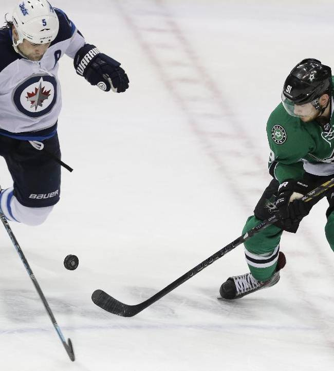 Dallas Stars center Tyler Seguin (91) an Winnipeg Jets defenseman Mark Stuart (5) position for control of the puck during the third period of an NHL hockey game Monday, March 24, 2014, in Dallas. The Stars won 2-1