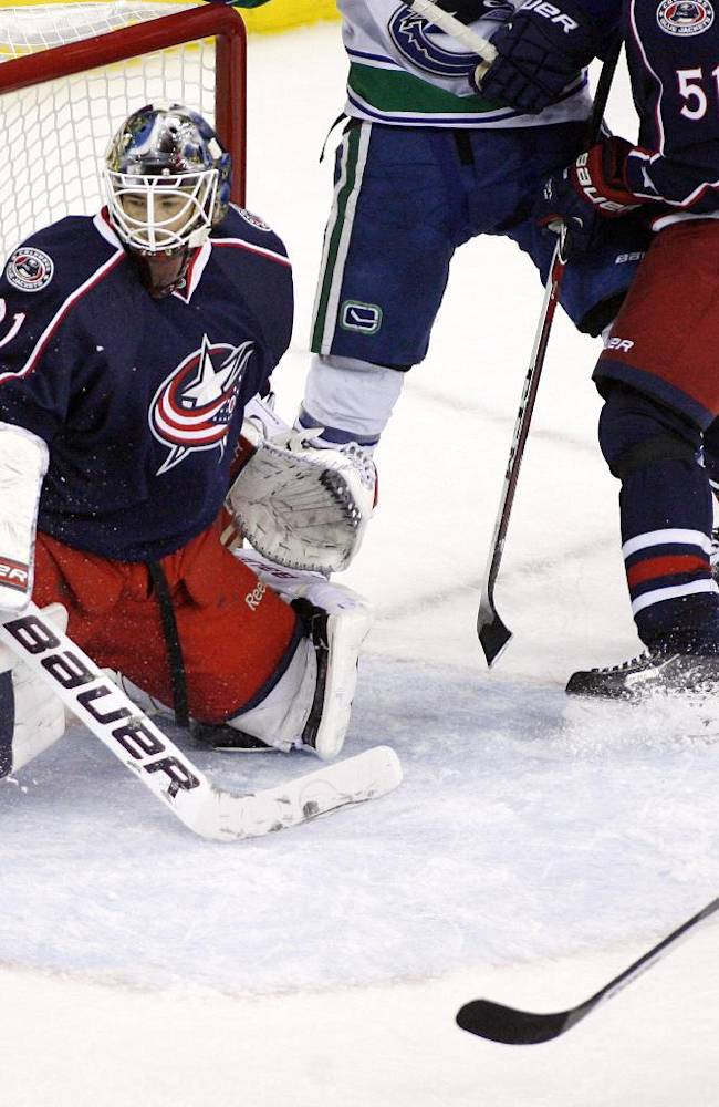 Columbus goalie Curtis McElhinney (31) blocks a shot in the final minute by Vancouver's Chris Higgins, right, during an NHL hockey game Sunday, Oct. 20, 2013, in Columbus, Ohio