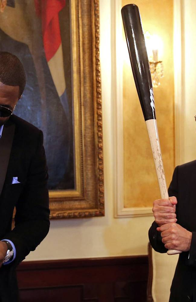 Boston Red Sox designated hitter David Ortiz, left, presents Dominican Republic President Danilo Medina with a ball and a bat during a meeting at the National Palace in Santo Domingo, Dominican Republic, Thursday, Nov. 28, 2013. Ortiz and fellow players of the Dominican Republic baseball team are in Santo Domingo to receive their champions rings for winning the 2013 World Baseball Classic in March