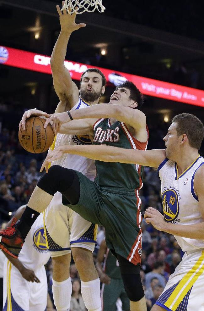 Milwaukee Bucks' Ersan Ilyasova, center, attempts to shoot between Golden State Warriors' Andrew Bogut, left, and David Lee during the first half of an NBA basketball game Thursday, March 20, 2014, in Oakland, Calif