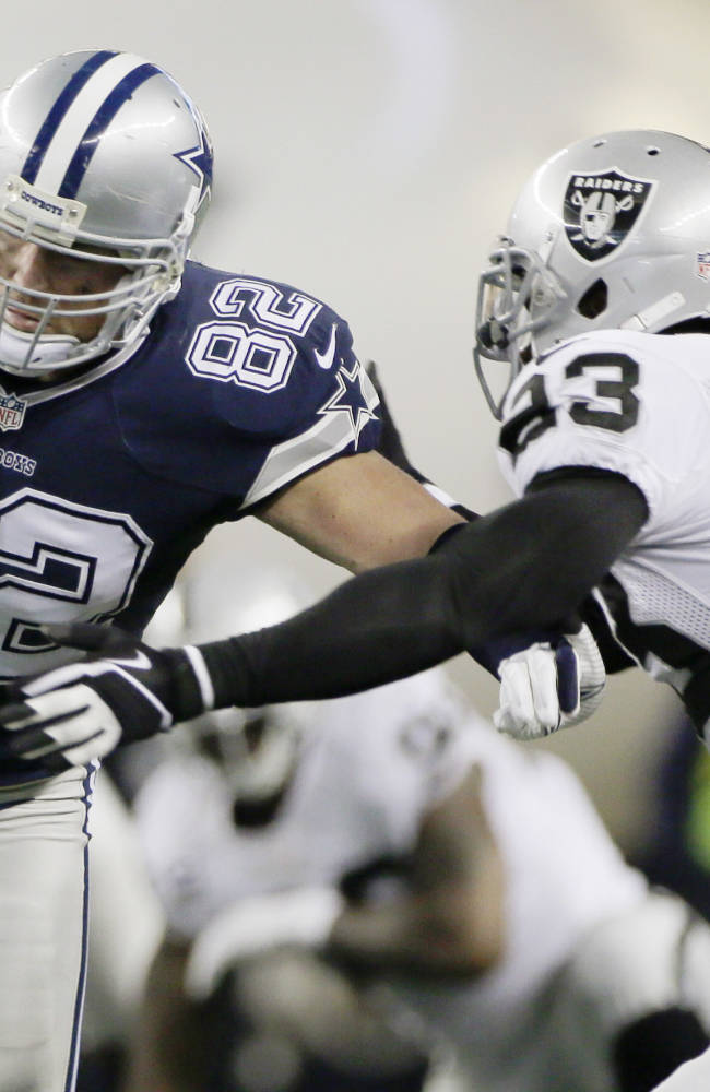 Dallas Cowboys tight end Jason Witten (82) is tackled by Oakland Raiders cornerback Tracy Porter (23) during the first half of an NFL football game, Thursday, Nov. 28, 2013, in Arlington, Texas