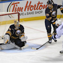 Buffalo Sabres goaltender Michal Neuvirth (34), of the Czech Republic, makes a save on Toronto Maple Leafs defenseman Dion Phaneuf (3) as Sabres' defenseman Tyson Strachan (24), looks on during the first period of an NHL hockey game Saturday, Nov. 15, 201