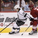 Los Angeles Kings' Mike Richards (10) tries to keep the puck away from Arizona Coyotes' Keith Yandle (3) during the first period of an NHL hockey game Saturday, Oct. 11, 2014, in Glendale, Ariz The Associated Press
