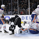 Los Angeles Kings' Dustin Brown (23) scores against Edmonton Oilers goalie Ben Scrivens (30) during the second period of an NHL hockey game Tuesday, Oct. 14, 2014, in Los Angeles The Associated Press