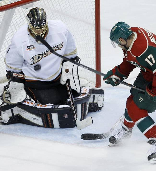 Anaheim Ducks goalie Jonas Hiller, left,  of Switzerland, stops a shot by Minnesota Wild center Torrey Mitchell (17) during the third period of an NHL hockey game in St. Paul, Minn., Saturday, Oct. 5, 2013. The Ducks defeated the Wild 4-3 in overtime