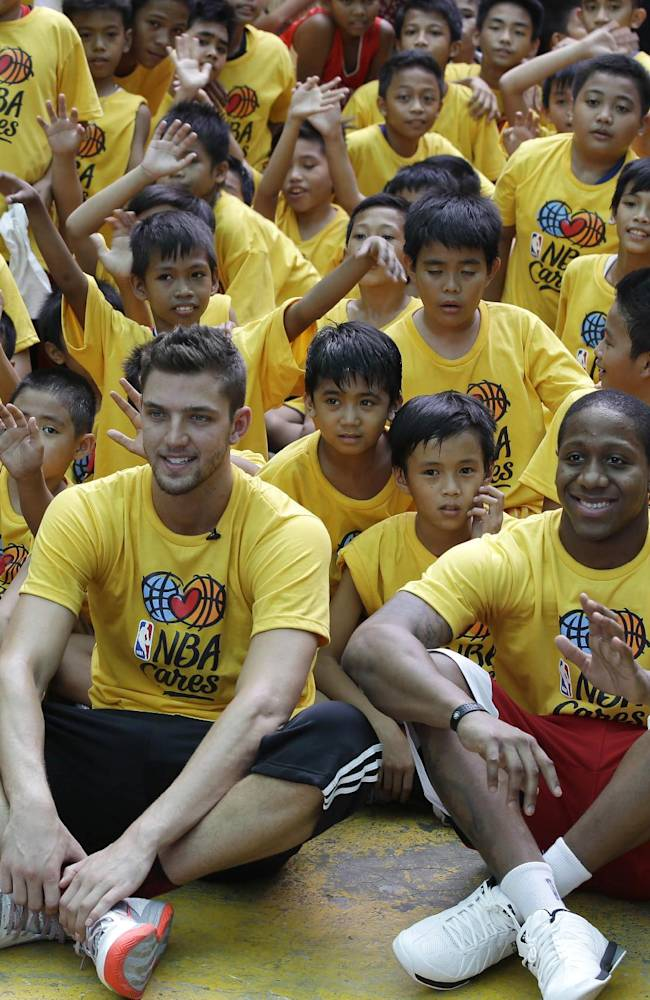 Houston Rockets' Chandler Parsons, front left, and Isaiah Canaan, front center, pose with elementary students following their basketball clinic at their campus Wednesday, Oct. 9, 2013, in Manila, Philippines. The Indiana Pacers will play against the Houston Rockets on Thursday in the first NBA game in this basketball-obsessed Southeast Asian nation, part of the NBA's global schedule that will have eight teams play in six countries this month