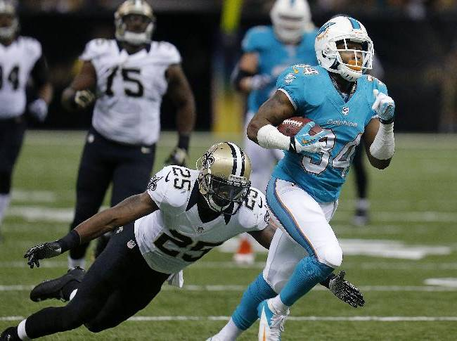 Miami Dolphins running back Marcus Thigpen (34) rushes past New Orleans Saints defensive back Rafael Bush (25) in the first half of an NFL football game in New Orleans, Monday, Sept. 30, 2013