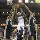 Sacramento Kings center DeMarcus Cousins, center, drives to the basket between San Antonio Spurs' Boris Diaw, left, of France and Kawhi Leonard during the third quarter of an NBA basketball game in Sacramento, Calif., Friday, March 21, 2014. The Spurs wo