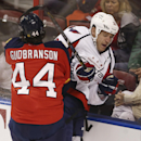 Florida Panthers' Erik Gudbranson (44) checks Washington Capitals' Brooks Laich (21) into the glass during the first period of an NHL hockey game, Thursday, Feb. 27, 2014, in Sunrise, Fla The Associated Press