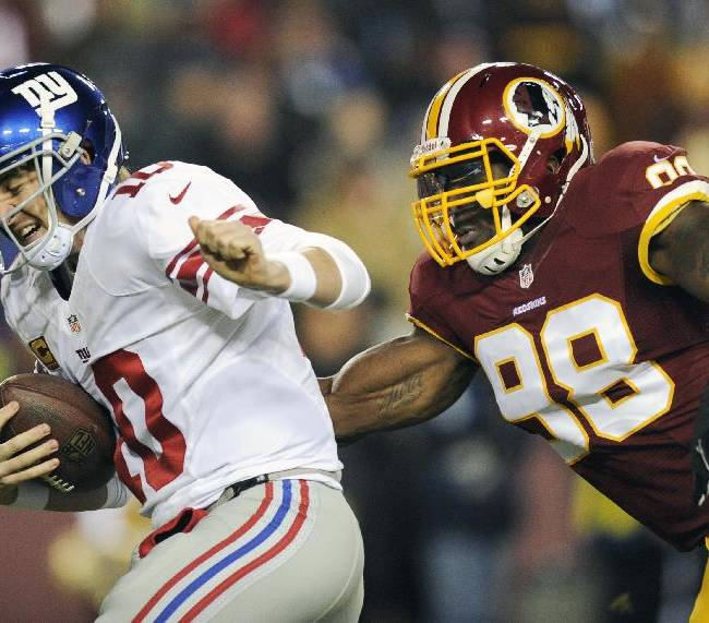 in this Dec. 1, 2013 file photo, New York Giants quarterback Eli Manning, left, is sacked by Washington Redskins outside linebacker Brian Orakpo (98) during the first half of an NFL football game in Landover, Md. The Redskins have used their franchise tag on three-time Pro Bowl linebacker  Orakpo, all but ensuring he will remain with the team next season. The Redskins used the non-exclusive tag Monday, March 3, 2014, on Orakpo