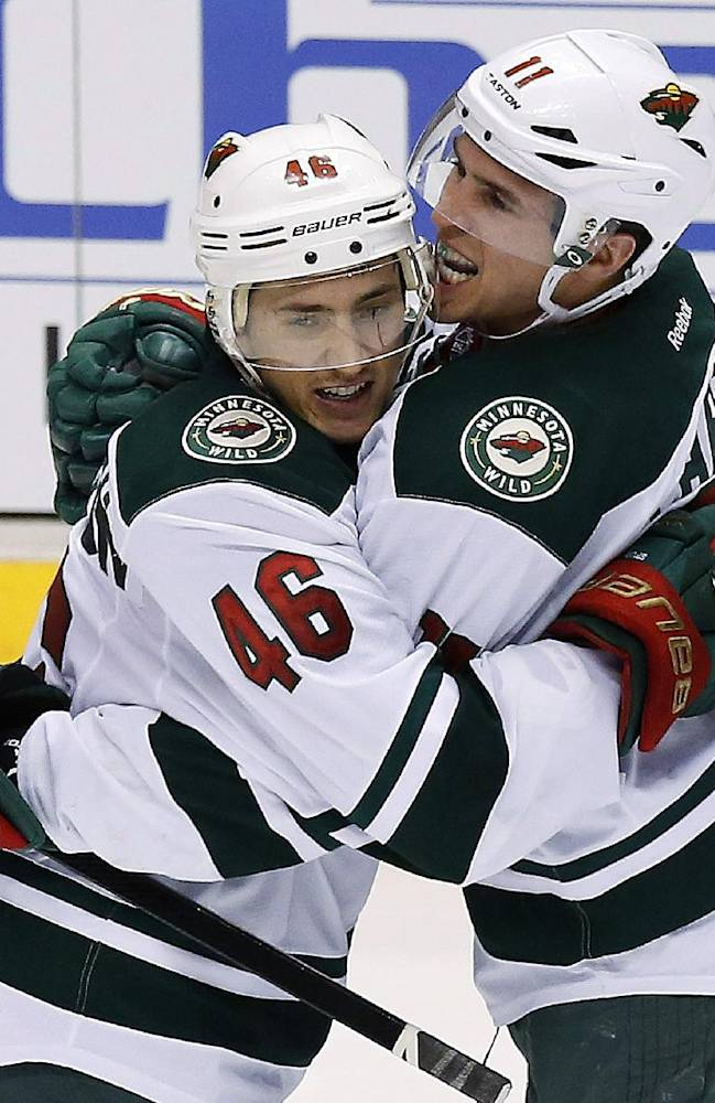 Minnesota Wild's Zach Parise (11) celebrates his goal against the Phoenix Coyotes with teammate Jared Spurgeon (46) during the third period of an NHL hockey game, Saturday, March 29, 2014, in Glendale, Ariz. The Wild defeated the Coyotes 3-1