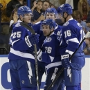 Tampa Bay Lightning defenseman Matt Carle (25) celebrates with teammates Martin St. Louis (26) and Teddy Purcell (16) after s