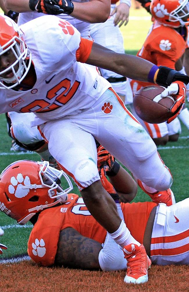 Clemson running back D.J. Howard (22) steps over defensive end Corey Crawford for a touchdown during an NCAA college football spring game at Memorial Stadium in Clemson, S.C., Saturday, April 12, 2014