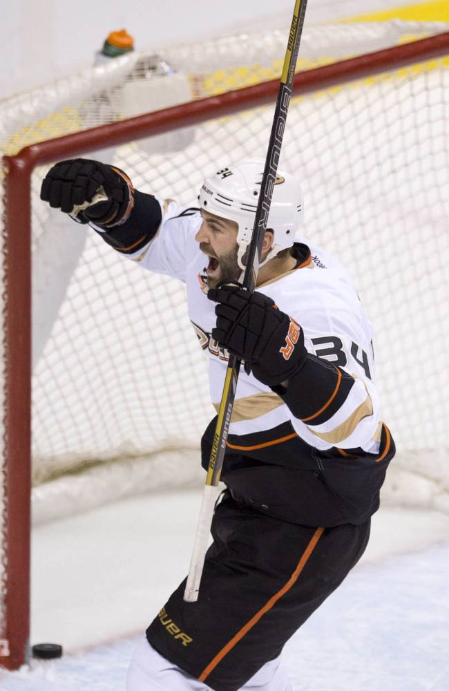 Anaheim Ducks right wing Daniel Winnik (34) celebrates teammate Kyle Palmieri's goal during the second period of NHL action against the Vancouver Canucks in Vancouver on Monday, April 7, 2014