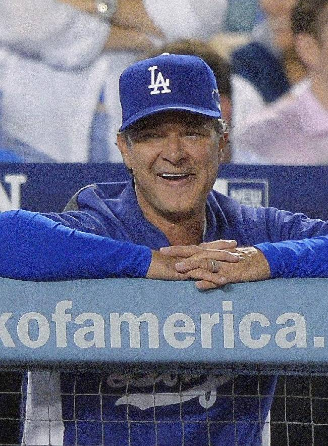 Los Angeles Dodgers manager Don Mattingly smiles during a pitching change in the eighth inning of Game 3 of the National League baseball championship series against the St. Louis Cardinals Monday, Oct. 14, 2013, in Los Angeles