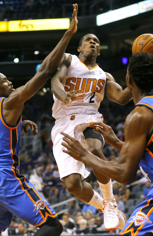 Phoenix Suns' Eric Bledsoe (2) drives past Oklahoma Thunder's Serge Ibaka (9), of Congo, and Hasheem Thabeet, of Tanzania,  during the second half of an NBA preseason basketball game, Tuesday, Oct. 22, 2013, in Phoenix