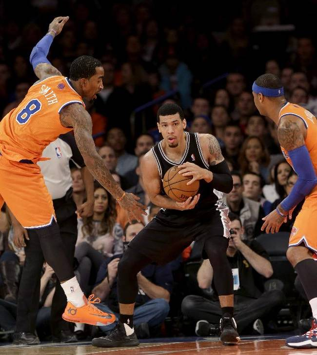San Antonio Spurs' Danny Green, center, keeps the ball from New York Knicks' J.R. Smith, left, and Carmelo Anthony during the first half of an NBA basketball game at Madison Square Garden, Sunday, Nov. 10, 2013, in New York