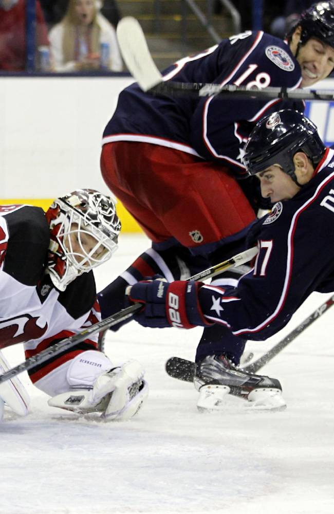 Columbus Blue Jackets' Brandon Dubinsky, right, scores against New Jersey Devils goalie Cory Schneider during the second period of an NHL hockey game in Columbus, Ohio, Tuesday, Oct. 22, 2013