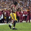 In this Jan. 6, 2013, photo, Washington Redskins quarterback Robert Griffin III (10) returns to the huddle after hurting his right knee as he fell awkwardly while throwing an incomplete pass during the first quarter of their NFL wild card playoff football game against the Seattle Seahawks in Landover, Md. An injury that sidelines Griffin well into next season is a very real possibility _ or at least it seemed that way Monday, Jan. 7, after head coach Mike Shanahan described the results of tests on the rookie's right knee following a series of plays in their Sunday game that did additional damage to a knee that was just three games removed from suffering a sprained lateral collateral ligament. (AP Photo/The Virginian-Pilot, L. Todd Spencer)