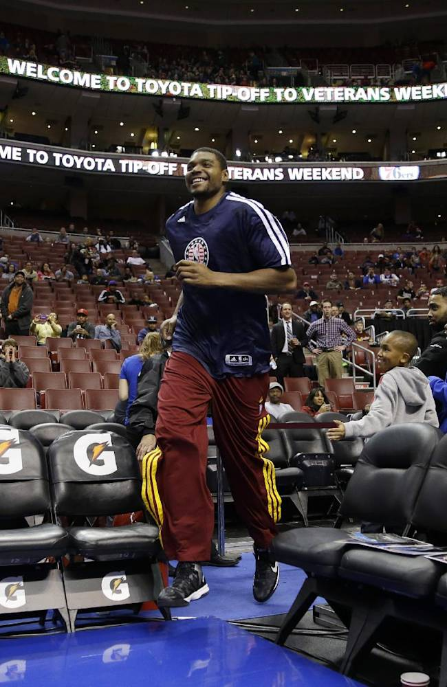 Cleveland Cavaliers' Andrew Bynum smiles as he runs onto the court for warm ups before an NBA basketball game against the Philadelphia 76ers, Friday, Nov. 8, 2013, in Philadelphia
