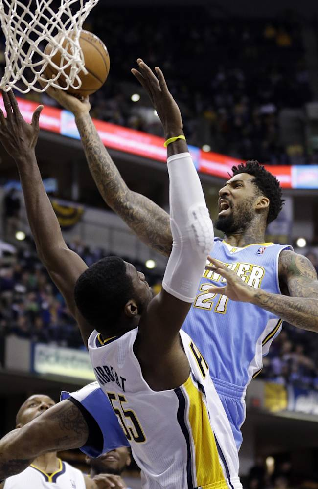 Denver Nuggets forward Wilson Chandler, right, gets a basket over Indiana Pacers center Roy Hibbert in the first half of an NBA basketball game in Indianapolis, Monday, Feb. 10, 2014
