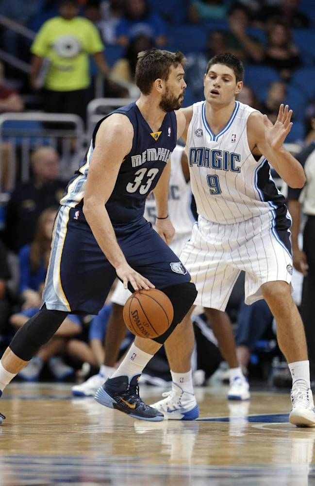 Memphis Grizzlies' Marc Gasol (33), of Spain, makes a move to the basket around Orlando Magic's Nikola Vucevic (9), of Montenegro, during the second half of an NBA preseason basketball game in Orlando, Fla., Friday, Oct. 18, 2013. The Memphis Grizzlies won the game 97-91