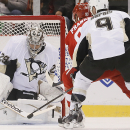 Pittsburgh Penguins goalie Marc-Andre Fleury (29) stops a Detroit Red Wings' Johan Franzen (93), of Sweden, shot as Pascal Dupuis (9) defends in the first period of a NHL preseason hockey game in Detroit Wednesday, Oct. 1, 2014. (AP Photo/Paul Sancya)