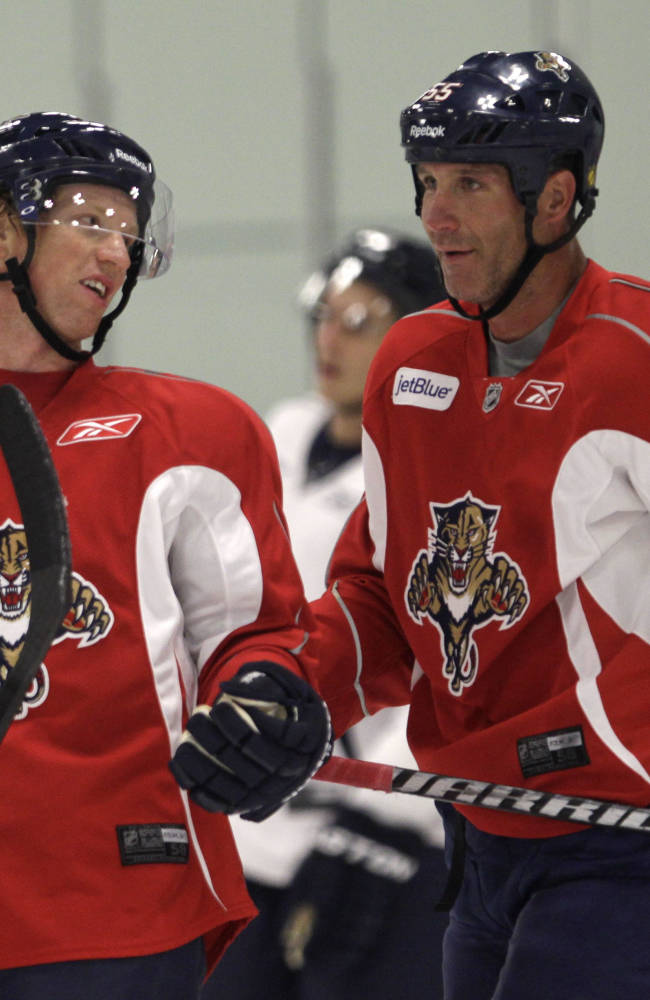 Florida Panthers defenseman Brian Campbell (51) and Ed Jovanovski (55) talk during NHL hockey training camp Thursday, Sept. 12, 2013, in Coral Springs, Fla
