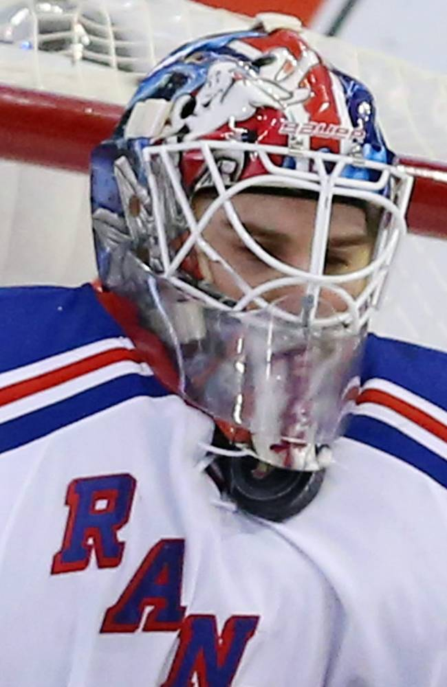 New York Rangers goaltender Cam Talbot (33) stops the puck under his facemask during the second period of an NHL hockey game against the Ottawa Senators in Ottawa, Saturday, Jan. 18, 2014