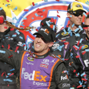 Denny Hamlin sprays cola after winning the NASCAR Sprint Cup Series auto race at Martinsville Speedway in Martinsville, Va., Sunday, March 29, 2015. (AP Photo/Steve Helber)