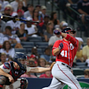 Washington Nationals' Sandy Leon (41) loses his bat as he swings during an at-bat against Atlanta Braves relief pitcher Anthony Varvaro as Braves catcher Evan Gattis, left, looks on in the sixth inning of a baseball game on Saturday, April 12, 2014, in At