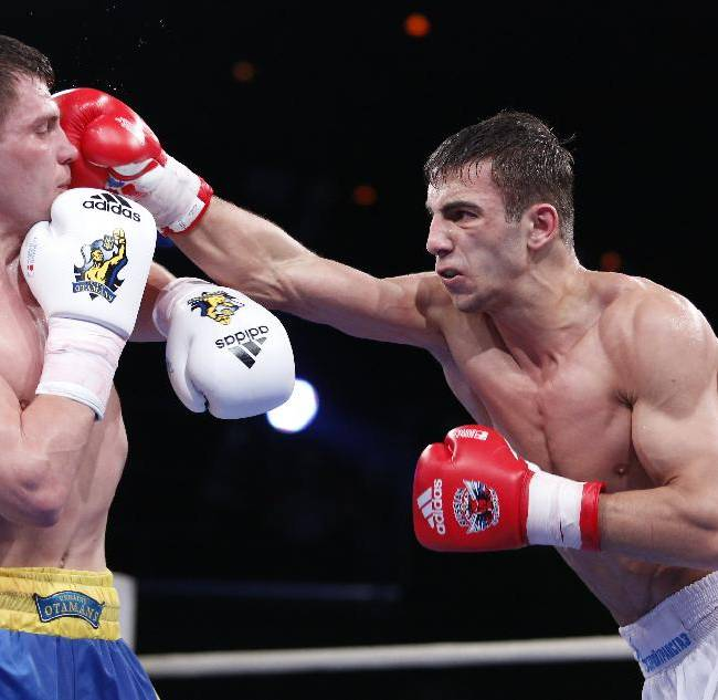 Russia's Radzhab Butaev, right, punches Ukraine's Denis Berinchyk during their light welterweight 64-kg World Series of Boxing quarterfinal bout between Russian Boxing Team and Ukraine Otamans, in Moscow, Russia, Monday, March, 31, 2014. Second leg matches will take part in Donetsk, Ukraine, on April 4
