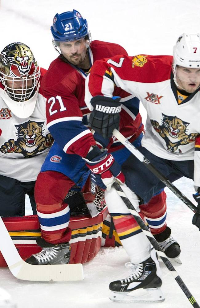 Montreal Canadiens' Brian Gionta (21) gets caught in between Florida Panthers goalie Tim Thomas and defenseman Dmitry Kulikov, right, during first period of an NHL hockey game, Monday, Jan. 6, 2014 in Montreal