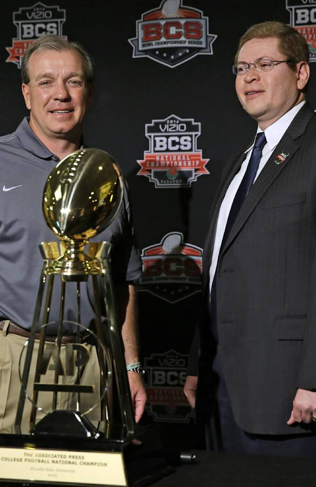 Florida State head coach Jimbo Fisher and Associated Press' Ed Montes pose with the AP College Football National Champion trophy during a news conference for the BCS National Championship NCAA college football game Tuesday, Jan. 7, 2014, in Newport Beach, Calif. Florida State beat Auburn 34-31 to win the championship the night before