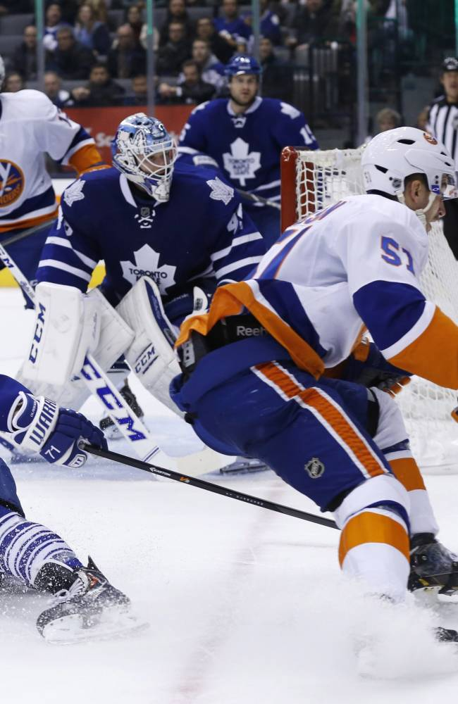 Toronto Maple Leafs' David Clarkson, left, defends against New York Islanders' Frans Nielsen during the third period of an NHL hockey hockey game, Tuesday, Nov. 19, 2013 in Toronto