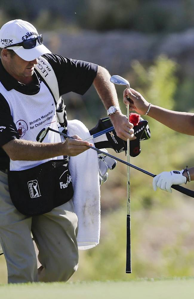 Ryo Ishikawa, right, grabs his putter after chipping onto the 15th green in the first round of the Shriners Hospitals for Children Open golf tournament, Thursday, Oct. 17, 2013, in Las Vegas