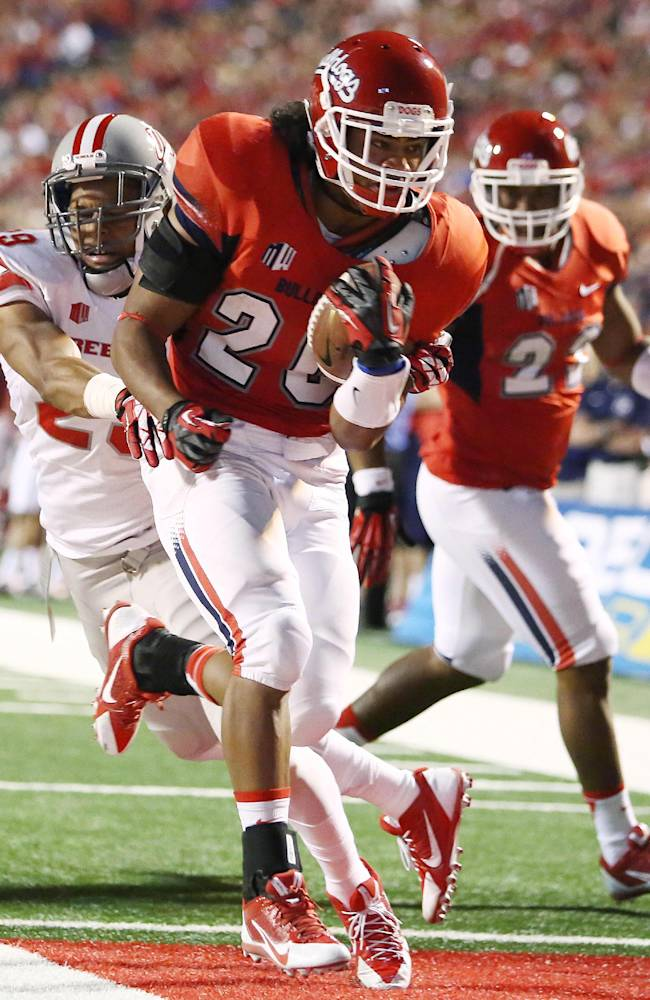 Fresno State's Josh Quezada (20) heads into the endzone for a touchdown and chased by UNLV'S Tajh Hasson (29) during the first half of an NCAA college football game Saturday, Oct. 19, 2013, in Fresno, Calif