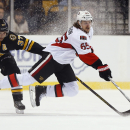 Ottawa Senators' Erik Karlsson keeps control of the puck while being tripped by Boston Bruins' Patrice Bergeron (37) during the third period of the Senators 3-2 shootout win in an NHL hockey game in Boston, Saturday, Dec. 13, 2014 The Associated Press