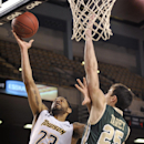 Towson's Mike Burwell, left, shoots as William and Mary's Terry Tarpey defends during the first half of the semifinal round of the CAA Championship NCAA basketball tournament Sunday, March 9, 2014, in Baltimore The Associated Press