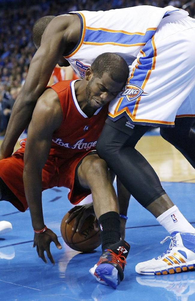 Los Angeles Clippers guard Chris Paul, bottom, fights with Oklahoma City Thunder forward Serge Ibaka, top, for the ball in the first quarter of an NBA basketball game in Oklahoma City, Thursday, Nov. 21, 2013