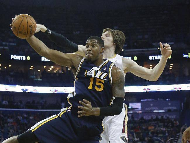Utah Jazz center Derrick Favors (15) grabs a rebound in front of New Orleans Pelicans forward Luke Babbitt (8) in the first half of an NBA basketball game in New Orleans, Friday, March 28, 2014