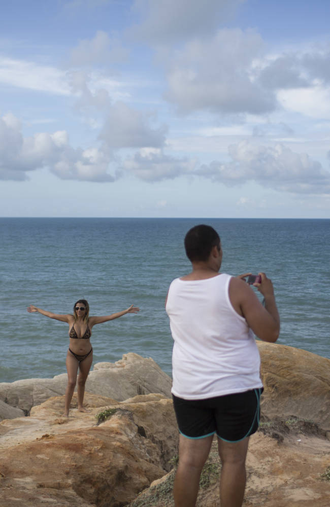 Tourists pose for photos on sea cliffs, or Falesias, in Beberibe, near Fortaleza, Brazil, Saturday, April 26, 2014. Beberibe is one of the coast cities located south-east of Fortaleza with many magnificent beaches popular with tourists. Fortaleza one of the host cities of the 2014 soccer World Cup