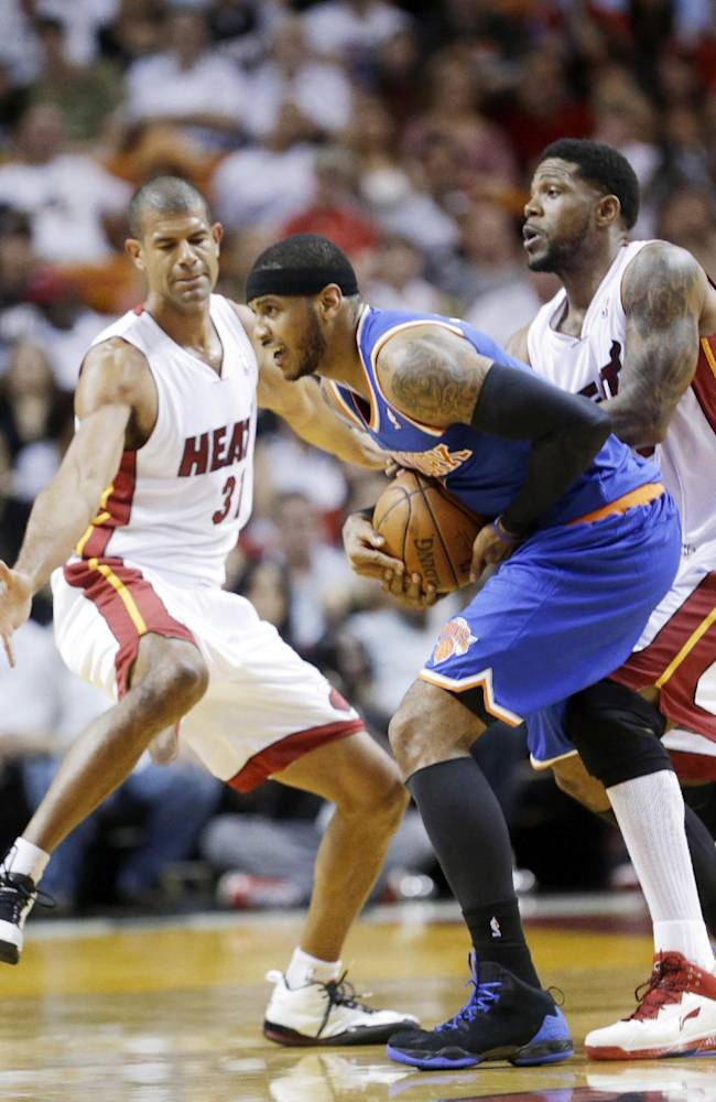 New York Knicks forward Carmelo Anthony, center, is fouled by Miami Heat forward Udonis Haslem, right, as forward Shane Battier, left, defends during the first half of an NBA basketball game, Sunday, April 6, 2014, in Miami