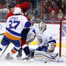 New York Islanders goalie Chad Johnson (30) moves to grab the puck as Washington Capitals center Brooks Laich (21) and defenseman Brian Strait (37) struggle nearby in the first period of an NHL hockey game, Friday, Nov. 28, 2014, in Washington The Associa