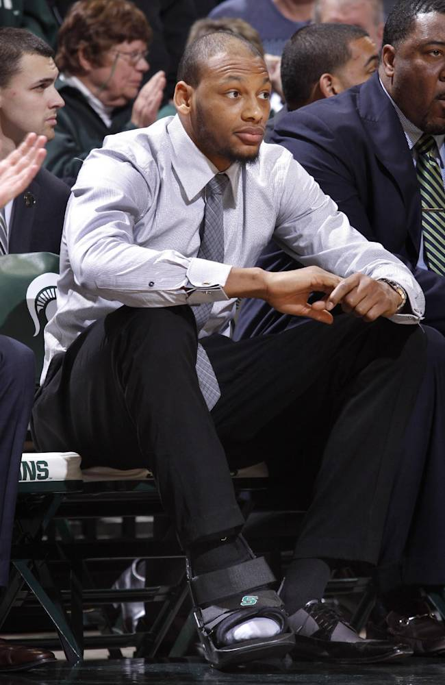 Michigan State's Adreian Payne sits on the bench in street clothes and a walking boot during the second half of an NCAA college basketball game against Michigan State, Saturday, Jan. 11, 2014, in East Lansing, Mich. Michigan State won 87-75 in overtime