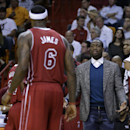 Miami Heat's Dwyane Wade, right, gestures to LeBron James (6) from the bench during the second half of an NBA basketball game against the Detroit Pistons, Tuesday, Dec. 3, 2013, in Miami. The Pistons won 107-97. Wade did not play due to soreness in his kn