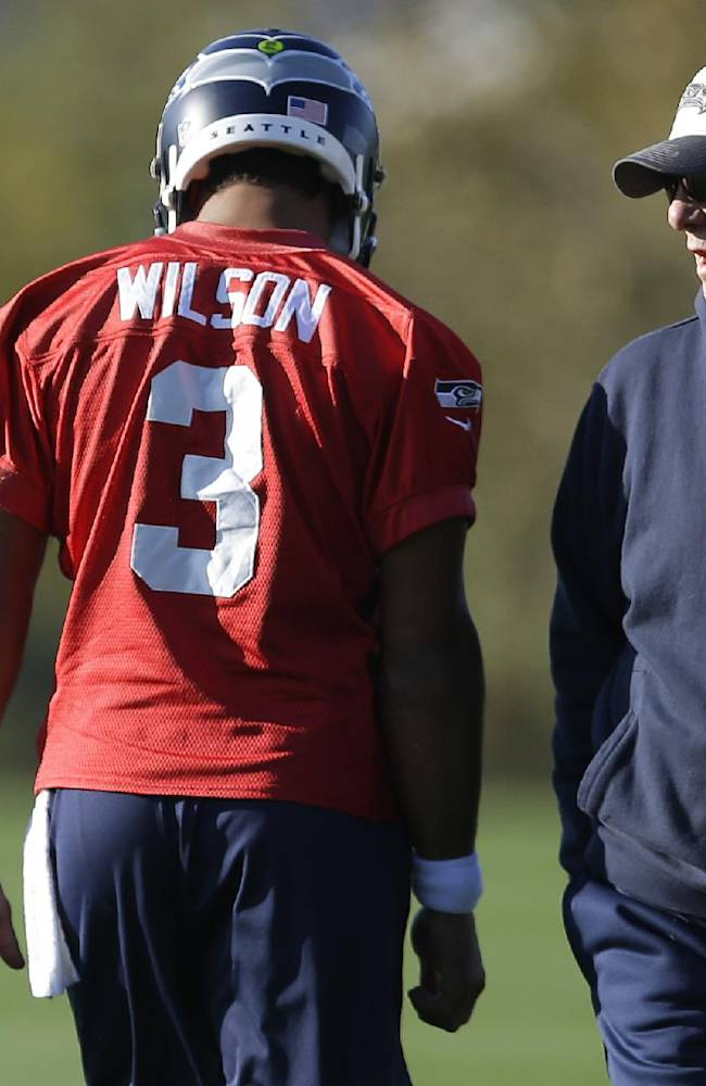 Seattle Seahawks quarterback Russell Wilson (3) talks with quarterbacks coach Carl Smith, right, at the start of NFL football practice, Tuesday, Oct. 22, 2013, in Renton, Wash