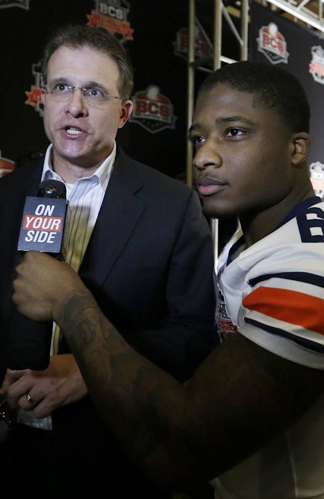 Auburn head coach Gus Malzahn is interviewed by player Jonathon Mincy during media day for the NCAA BCS National Championship college football game Saturday, Jan. 4, 2014, in Newport Beach, Calif. Florida State plays Auburn on Monday, Jan. 6, 2014