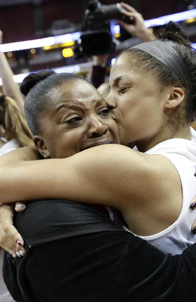 Cal State Northridge's Ashlee Guay, right, kisses her mother, Dana, as they celebrate the team's 73-58 win against Cal Poly after their NCAA college basketball championship game of the Big West Conference tournament, on Saturday, March 15, 2014, in Anaheim, Calif